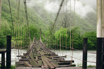 Fototapeta Współczesny Suspension bridge over the mountain river