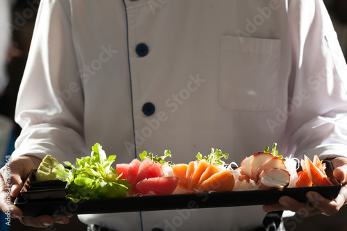 Photo  sashimi, a chef uniform holding a dish of Japanese Sashimi