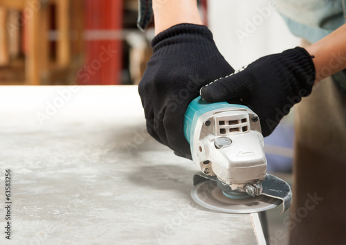 Canvas Print grinder worker cuts a stone the electric tool worker is tiling a