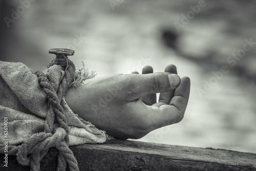 Genagelte Hand auf hölzernem Kreuz. Fototapete