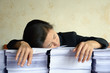 businesswoman tired and exhausted on pile of papers