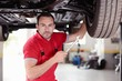 Mechanic with tool checking car
