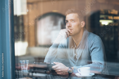 Fotomural Pensive young man using tablet computer in coffee shop