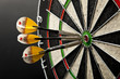 Three darts in bullseye of dartboard