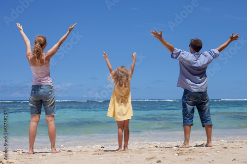 Spoed Foto op Canvas Bedehuis Happy family standing on the beach in the day time