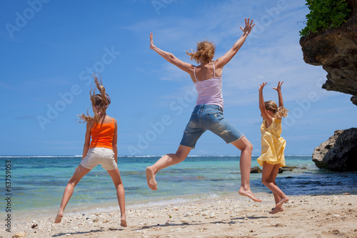 Spoed Foto op Canvas Bedehuis Happy family jumping at the beach in the day time