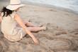 Woman beach drawing heart sand