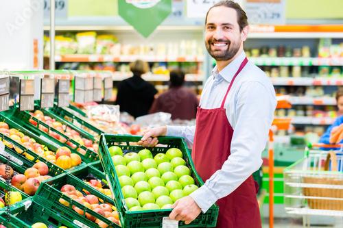 Fotografie, Obraz  Supermarkt Angestellter füllt Regale auf
