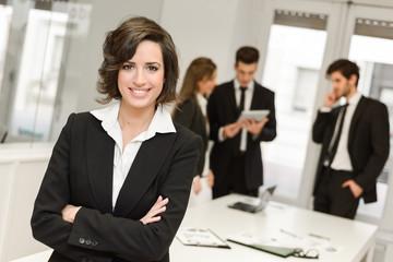 Naklejka Business leader looking at camera in working environment