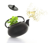 Teapot with green herbs and tea splash isolated