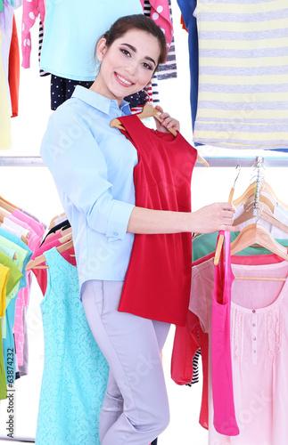 Fotobehang Art Studio Young woman choose clothes near rack with hangers