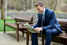 Smiling Businessman Reading Ne...