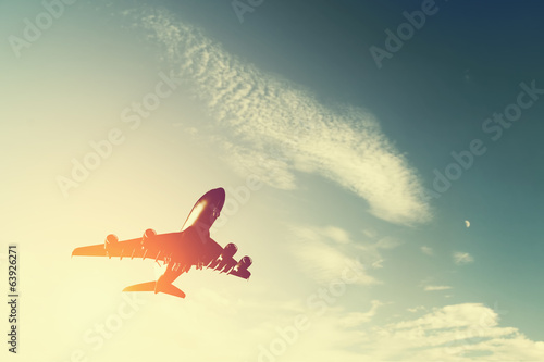 Airplane taking off at sunset. Silhouette of a flying aircraft