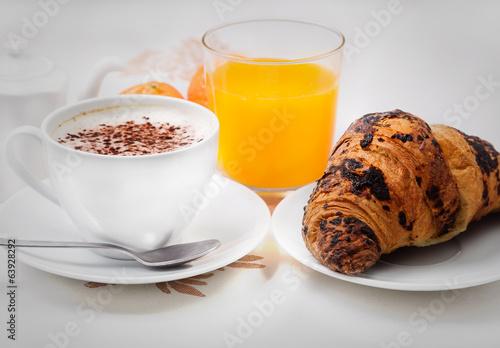 Fotografering  Cappuccino brioche e succo di Frutta