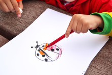 Child Painting A Ladybug