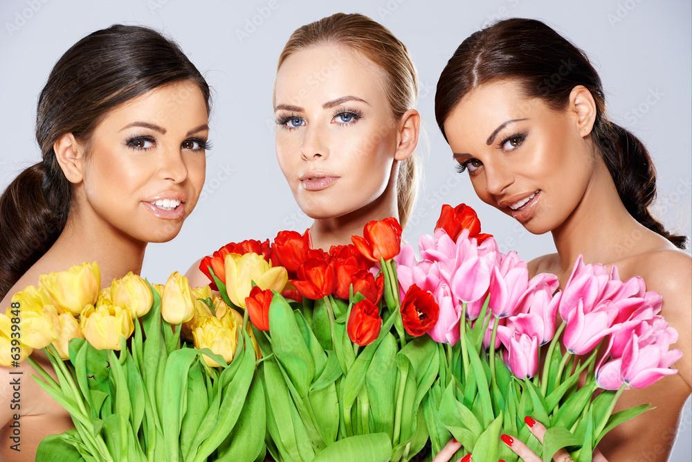 Trzy pięknej kobiety z świeżymi wiosna tulipanami
