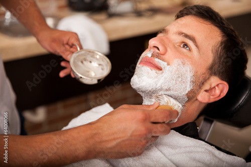 Getting shaved in a barber shop Canvas Print