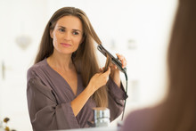 Young Woman Straightening Hair...