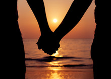 Silhouettes Couples Holding Hands On Sunset.