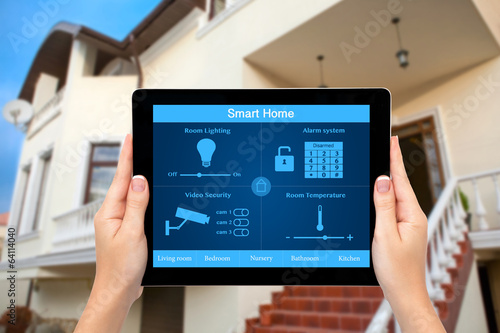 Fotografía  Female hands hold a tablet with system smart house on the backgr