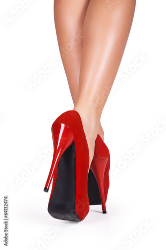 Fotografia  Woman legs wearing red high heels isolated on white background.