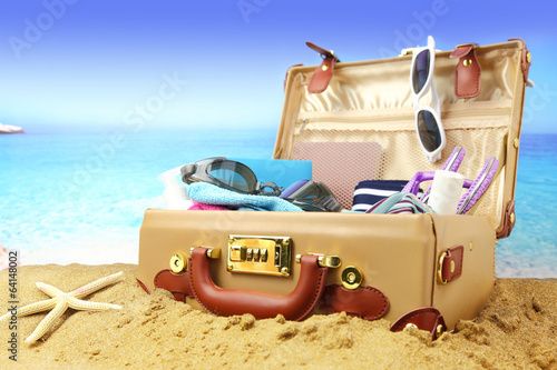 Photo  Full open suitcase on tropical beach background.