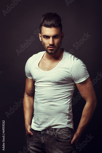 Handsome man posing in studio on dark background Canvas Print