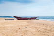 Traditional Sri Lankan fishing boat on empty sandy beach.