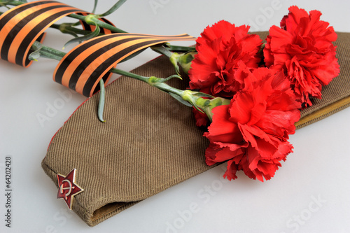 Fotografia  Military cap, carnations tied with Saint George ribbon on gray