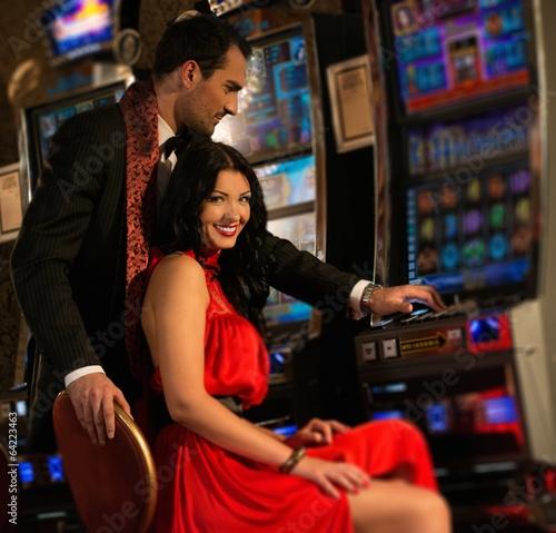 Spoed Foto op Canvas Muziekwinkel Beautiful young couple near slot machine in a casino