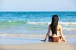beautiful woman in bikini sitting on the beach at summer day