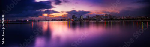 Cityscape sunset with reflection in the sea