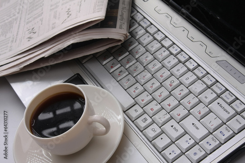 Photo coffee cup on a newspaper near the laptop