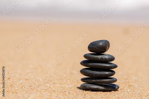 Valokuva  Zen stones jy on the sandy beach near the sea.