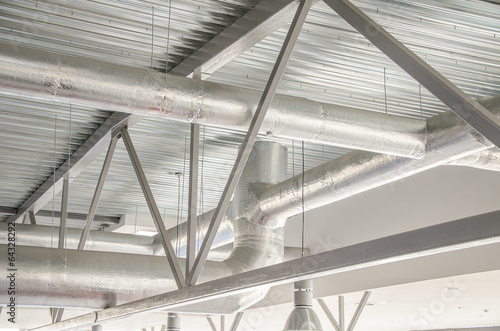 Photo Industrial steel ventilation pipes inside of building.