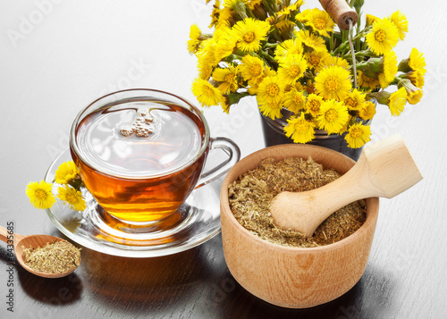 Valokuva  healthy tea, bucket with coltsfoot flowers and mortar on table