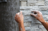 Fototapeta Kamienie - worker install stone wall surface with cement for house
