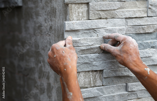 Fotomural worker install stone wall surface with cement for house