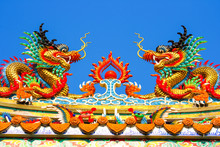 Twin Dragon Statues In Chinese Style On Top Of  Temple Roof