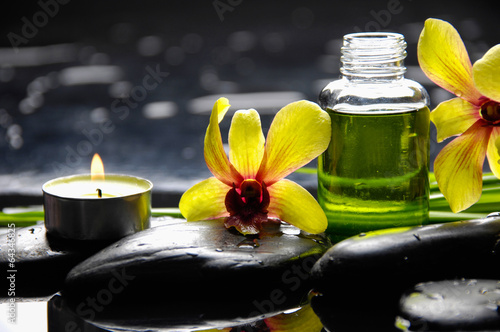 Poster Spa Yellow orchid with pebbles and massage oil ,leaf on wet