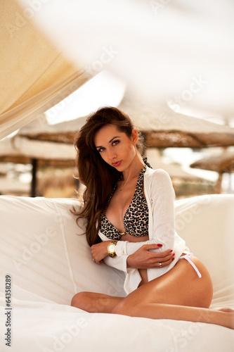 Obraz Attractive brunette alluring woman relaxing on a beach - fototapety do salonu