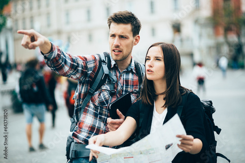 Fotomural Tourists looking for landmarks in city using map