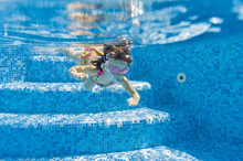 Happy Active Underwater Child Swims In Pool And Having Fun