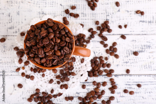 Cup full of coffee beans on light wooden background