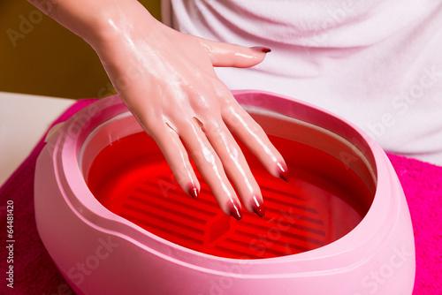 Fotografia Female hand and orange paraffin wax in bowl.
