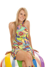 Woman In Colorful Dress Sitting On Colorful Ball