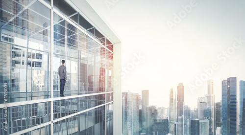 Fotografía  Businessman standing on a balcony and looking at city