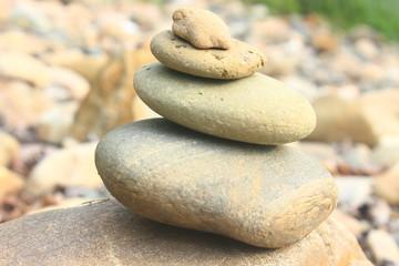 Fototapeta na wymiar Stones pyramid near small river symbolizing zen