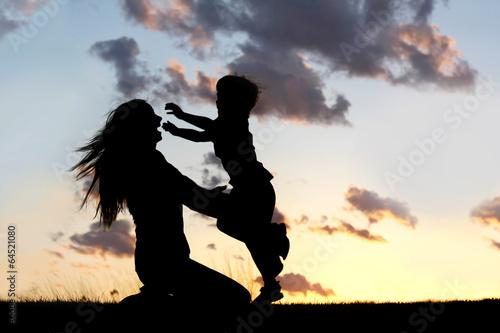 Fotografie, Obraz  Silhouette of Child Running to Hug Mother at Sunset