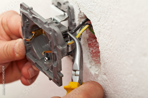 Fotografía  Electrician hands installing wires into electrical outlet